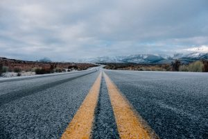 slightly icy road with snowy mountains in distance