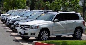 weston auto gallery sales lot showing line of pre-owned vehicles during the day